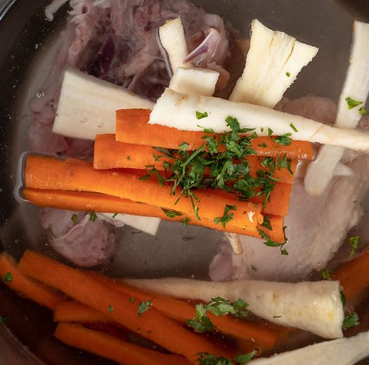 chicken frame in stock pot with carrots, parsnip, and parsley