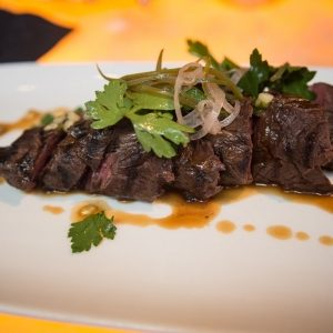 hanger steak topped with a heavy garnish of cilantro and pickled red onions