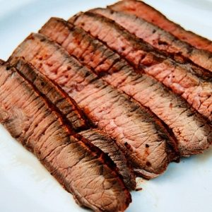 London broil cooked medium-rare, sliced, and arranged on a plate