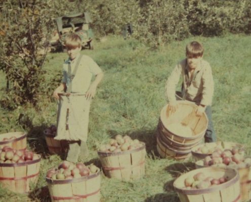 faded photo of two boys with apples