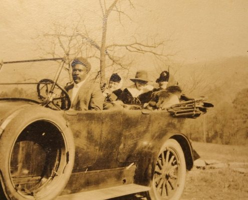 Old faded photo of three women and man in an old car