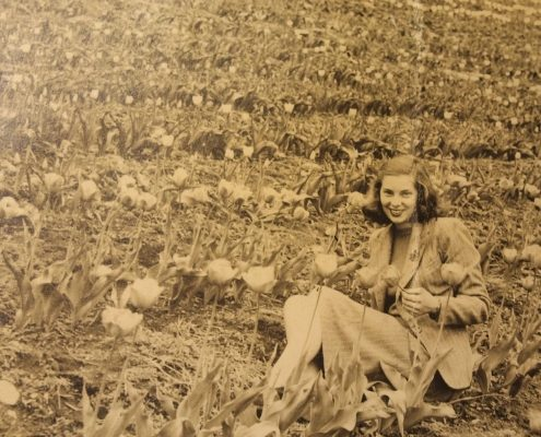 Old photo of young woman in field farming