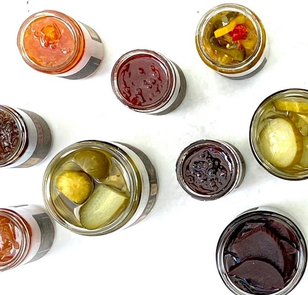 jars of colorful pickles and jams photographed from above on a white table
