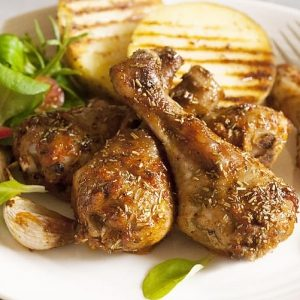 baked chicken drumsticks seasoned with herbs on a bed of sliced yellow summer squash and micro greens, white plate